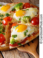 Sliced pizza with eggs, broccoli, tomatoes and parsley close-up. Vertical
