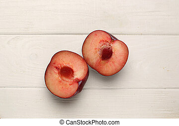 Sliced plum on the table. Close up. White background