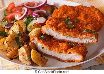 Sliced pork schnitzel, salad and fried potatoes close-up. horizontal