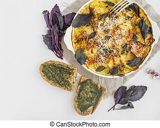 Sliced potato baked with cheese and basil in the oven