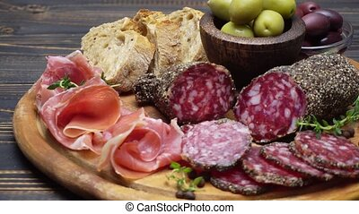 sliced prosciutto and salami sausage on a wooden board -...