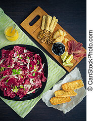 Sliced prosciutto with salad and toasts