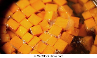 sliced pumpkin cubes in boiling