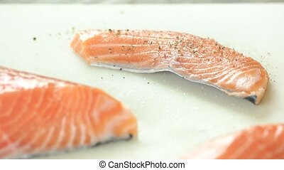 Sliced raw salmon with pepper. Uncooked fish close up.