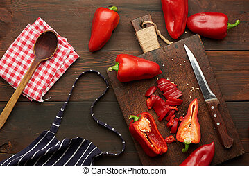 sliced red pepper on a wooden board, brown wooden table