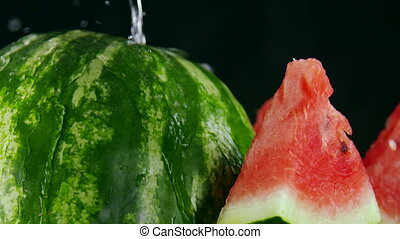Sliced red watermelon with splashes of water in slow motion on black background