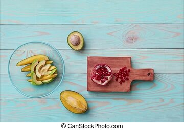 Sliced ripe fresh mango fruit, avocado, pomegranate, orange...