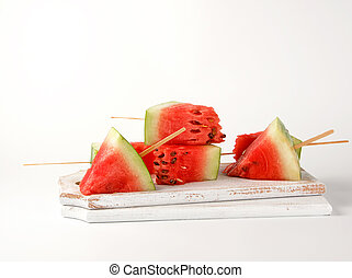 sliced ripe red watermelon with seeds on a wooden white cutting board