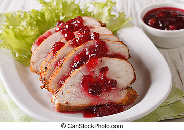 Sliced roasted turkey breast with cranberry sauce on a plate close-up. Horizontal