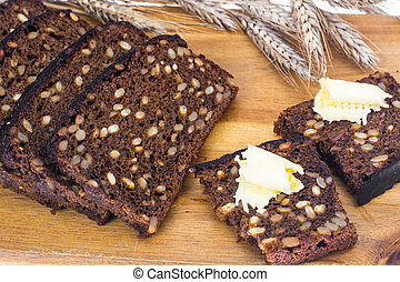 Sliced rye bread with sunflower seeds and butter