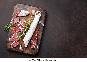 Sliced salami on cutting board. Top view with space for your...