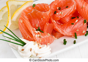 Sliced ??salmon with  onions on a white plate