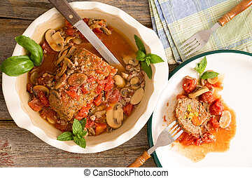 Sliced savory meatloaf with mushrooms and vegetables served in a casserole on a rustic wooden table with grungy peeling red paint, overhead view, copy space on the left