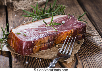 Sliced Smoked Ham with some fresh herbs on rustic wooden...