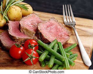Photo of steak dinner with thick slices of sirloin, cherry tomatoes, green beans and potatoes on a wooden board.