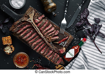 Sliced Steak T-bone lying on wooden board. Grilled vegetables in a pan grill. Black table with gray cloth