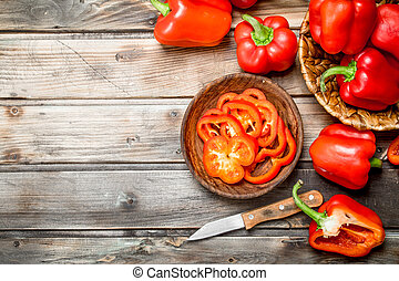 Sliced sweet pepper in bowl with knife and pepper in basket.