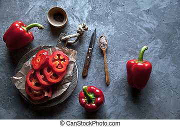Sliced sweet pepper on a cutting Board with a knife and ripe pepper.