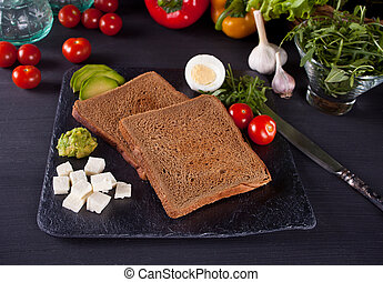 Sliced Toast Bread on black plate with vegetables