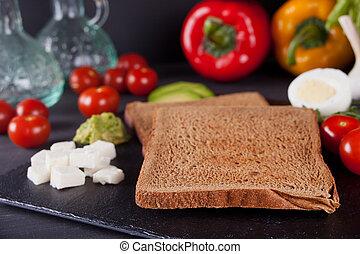 Sliced Toast Bread on black plate with vegetables