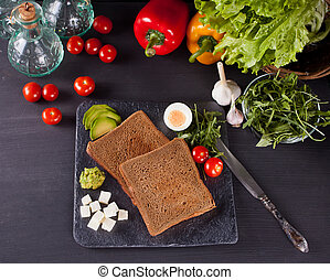 Sliced Toast Bread on black plate with vegetables. Top view.