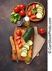 Sliced tomato and cucumber on cutting board