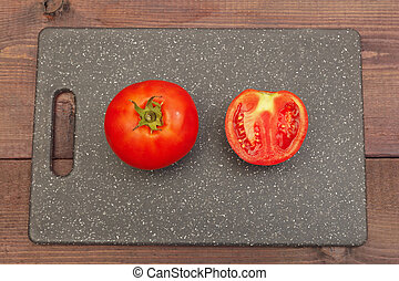 Sliced tomato on cutting board on wooden table. View from above.