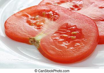 sliced tomato on white plate.