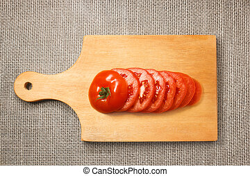 Sliced tomato on wooden cutting board with sacking