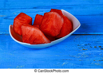 Sliced watermelon Top View. Many slices on an old rustic blue table. Side composition with copy space.