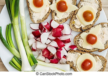 Sliced whole wheat bread with butter, cheese, cherry tomatoes, radish and onion, breakfast theme