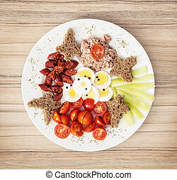 Sliced whole wheat bread with butter, tuna, sausage, cherry tomatoes, paprika and eggs