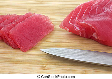 Sliced yellowfin tuna on cutting board - Close view of...