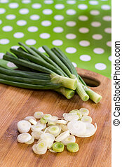 Sliced young onions on the wooden cutting board