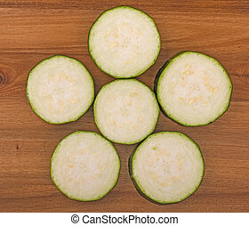 Sliced zucchini on a wooden board surface, top view, close up.