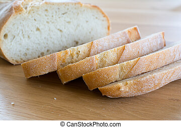 Slices and loaf of bread on wooden table.