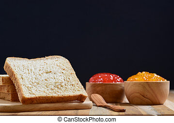 slices bread with jam on wooden table