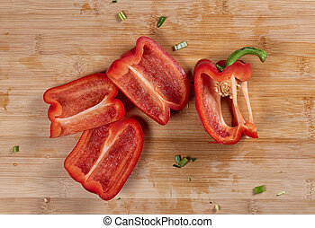 slices of a red bell pepper on wooden cutting board