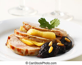 Slices of a turkey roll served with apple, plums and pine nuts