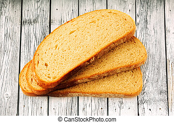 Slices of bread on wooden background