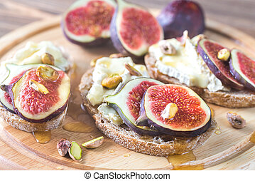 Slices of bread with camembert, figs and pistachios