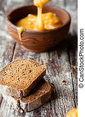 slices of brown bread and honey in a clay bowl
