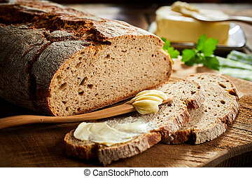 Slices of buttered rye bread with loaf