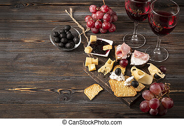 cheese, cracker, ham, jam, grapes, olives, 2 glasses of red wine on a dark wooden background, appetizer, tapas