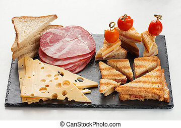 Slices of cheese, ham, bread and hot marinated cherry...