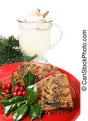 Closeup of delicious Christmas fruitcake garnished with Holly and a mug of egg nog in the background. Isolated on white.