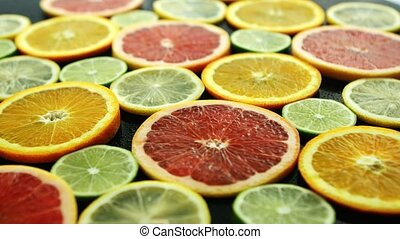 Slices of citruses on dark table - Closeup shot of assorted...