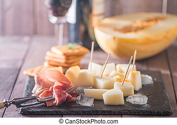 slices of cured ham with melon and red wine - spanish tapas...