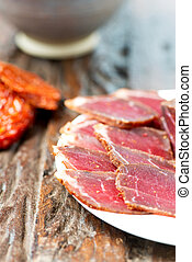 Slices of cured meet on plate vertical