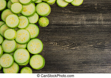 Slices of fresh green squash, zucchini, courgette  on wooden background